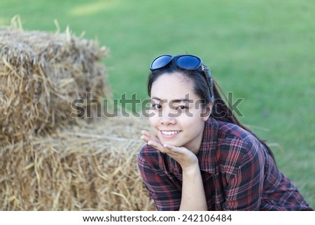 Smiling farmer asia woman sitting on straw in the farm - stock photo