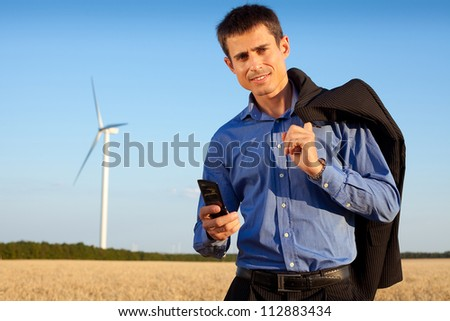 smiling farmer (businessman) standing in wheat field over wind turbines background and holding his mobile phone and jacket over shoulder