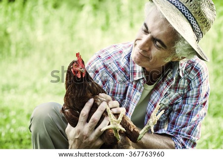 Smiling farmer in the field holding a chicken, healthy lifestyle and organic farming concept - stock photo