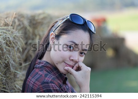 Smiling farmer woman standing by outside the straw fence of the farm - stock photo