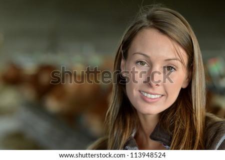 Smiling farmer woman standing in barn - stock photo