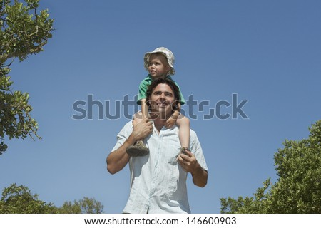 Smiling farther carrying son on shoulders against the clear blue sky