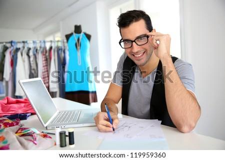 Smiling fashion designer in workshop - stock photo