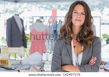 Smiling fashion designer with arms folded in a bright creative office - stock photo