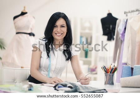 Smiling fashion designer working at her desk.