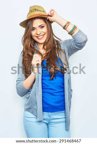 Smiling fashion model posing against white background. Beautiful young woman in street style dressed.