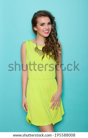 Smiling fashion model posing. Beautiful girl in lime green dress standing and looking at camera. Three quarter length studio shot on teal background. - stock photo