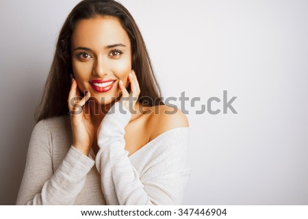 Smiling fashion woman with long hair and red lips posing over white background. Toned in warm colors. Studio shot, horizontal. - stock photo