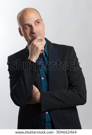 Smiling fashionable bald man thinking and looking up - stock photo