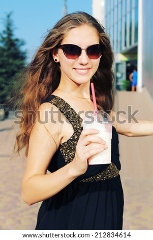 Smiling fashionable blonde drinking drinking a strawberry milkshake outdoors. Photo toned style Instagram filters