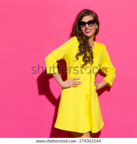 Smiling Fashionable Girl Against Pink Wall. Smiling beautiful girl in yellow mini dress posing against pink background. Three quarter length studio shot. - stock photo