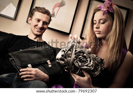 Smiling fashionable rich attractive couple sitting on sofa at home - stock photo