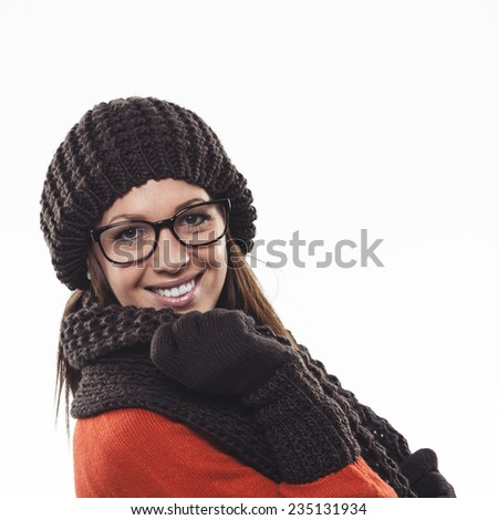 Smiling fashionable winter woman in glasses wearing a brown overcoat, scarf and gloves looking at the camera with a beaming smile, on white with copy space