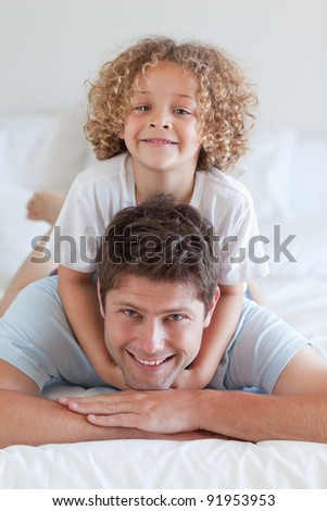 Smiling father and child lying on bed together - stock photo