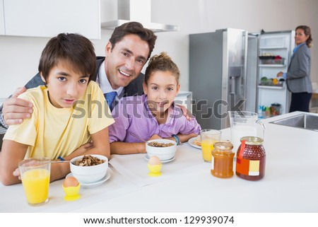 Smiling father and children having breakfast with mother standing at fridge - stock photo
