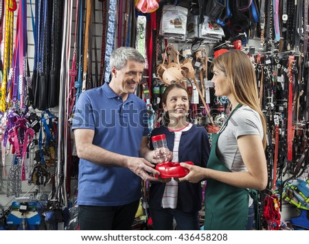 Smiling Father And Daughter Buying Pet Food Bowl From Saleswoman