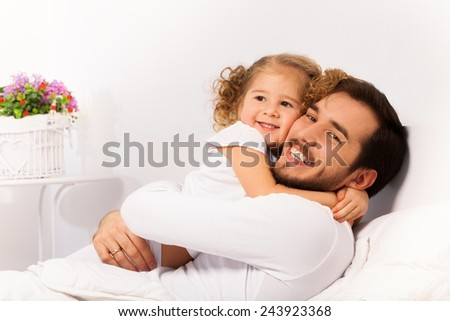 Smiling father and daughter hug on the white bed - stock photo