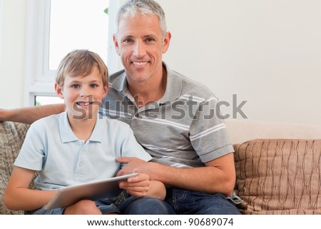 Smiling father and his son using a tablet computer in a living room - stock photo