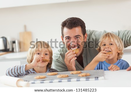 Smiling father and his sons eating cookies in the kitchen