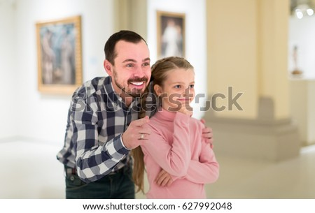 Smiling father and small daughter exploring art paintings in halls of museum
