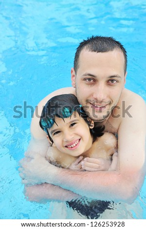 Smiling father and son leaning in the water pool - stock photo