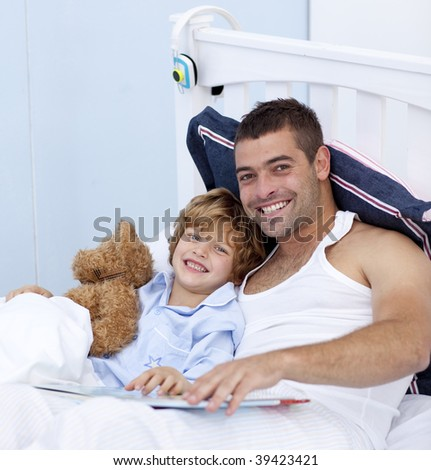 Smiling father and son reading a book in bed together