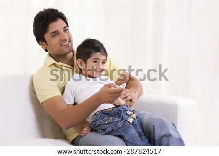Smiling father and son watching television
