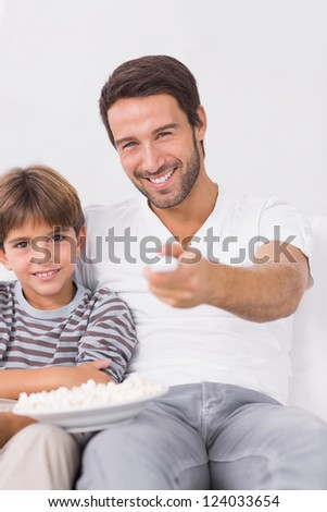 Smiling father and son watching tv together on the couch - stock photo