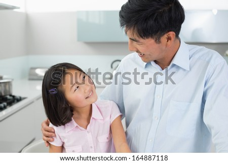 Smiling father and young daughter in the kitchen at home