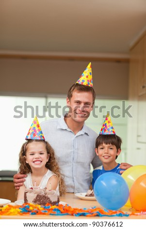 Smiling father celebrating with his kids - stock photo