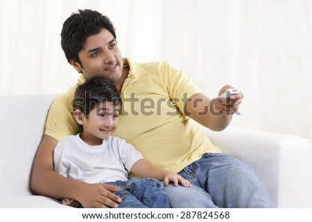 Smiling father changing channels while sitting with his son
