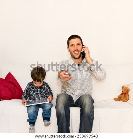 Smiling father making a joke with phone and tv remote control while son is playing with tablet on a white sofa with a red pillow and a bear toy - stock photo