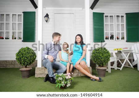 Smiling father, mother and daughter sit on porch of their new cottage. - stock photo