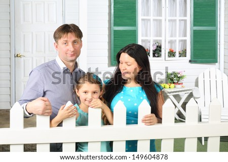 Smiling father, mother and little daughter stand next to white fence of cottage.