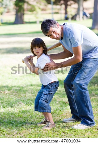 Smiling father playing baseball with his son in the park