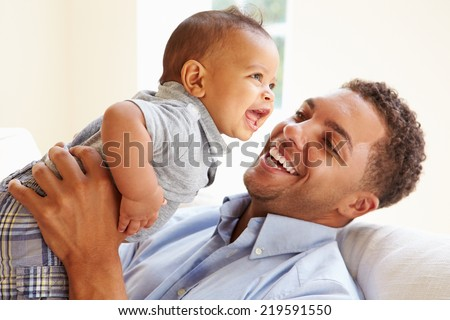 Smiling Father Playing With Baby Son At Home - stock photo