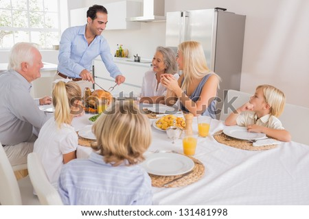 Smiling father proposing a slice of turkey for thanksgiving dinner - stock photo