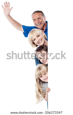 Smiling father raising his arm, family posing together