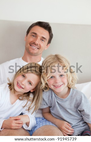 Smiling father sitting the bed together with his children