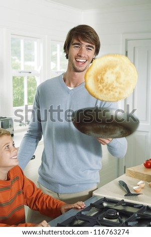 Smiling father tossing pancakes as he shows off to his young son as they prepare breakfast or dessert