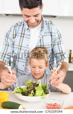 Smiling father tossing salad with his son at home in kitchen - stock photo