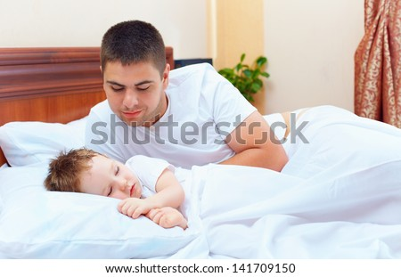 smiling father watching the son sleeps