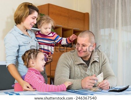 Smiling father with banknotes sitting at table, happy family staying nearby. Focus on girl - stock photo