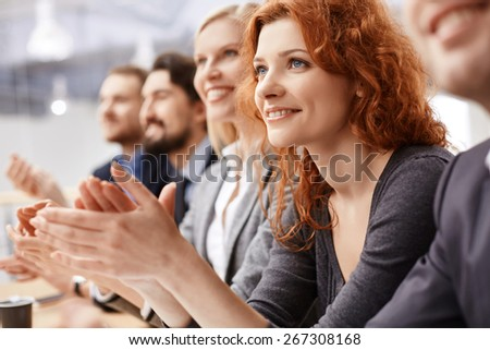 Smiling female applauding at conference between her colleagues - stock photo