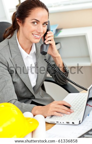 Smiling female architect talking on phone and using her laptop in her office at her desk - stock photo