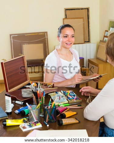 Smiling female artist painting portrait of mature woman at art studio with pencil and paints - stock photo