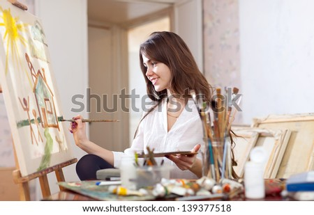 Smiling female artist paints picture on canvas with oil paints - stock photo