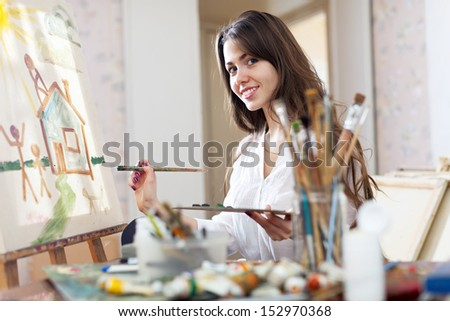 Smiling female artist paints picture on canvas with oil paints in her stidio - stock photo