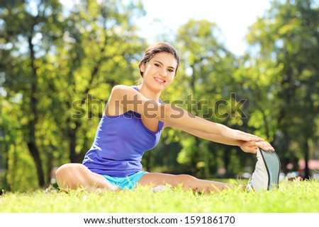 Smiling female athlete sitting on an excercising mat and stretching in a park - stock photo