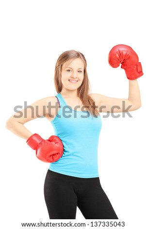 Smiling female athlete wearing red boxing gloves and posing isolated on white background